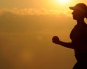 Eine Frau joggt bei Sonnenaufgang
