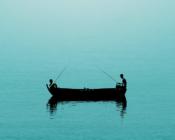 Zwei junge Fischer allein auf einem Boot im Meer